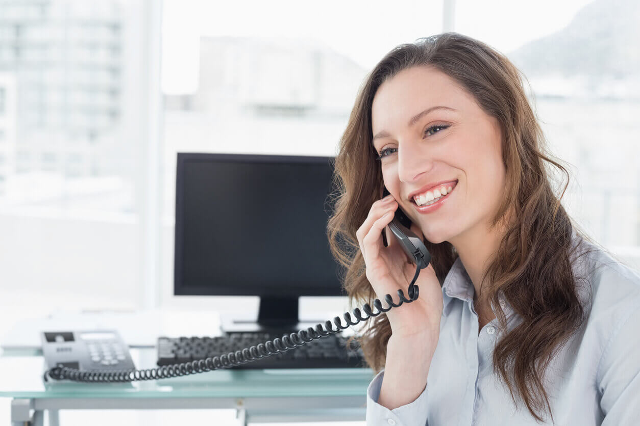 female on phone call in front of computer